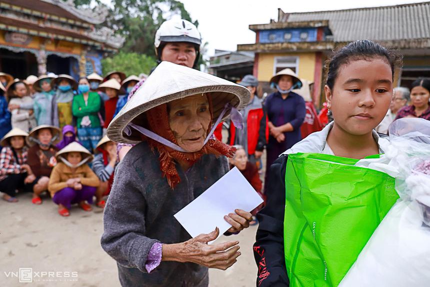 Cụ Nguyễn Thị In, 88 tuổi, ở thôn An Xuân Tây, xã Quảng An sức yếu nên nhờ cháu gái đi bê quà. Cụ kể, mưa lũ làm hai tạ thóc của gia đình ướt hết, đàn gà cũng bị cuốn trôi. Có 500.000 đồng tiền mặt trên tay, cụ định mua gà con về gây lại.