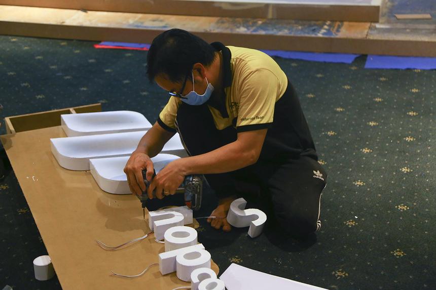 Anh Vũ Trần Hoàng Giang đang gắn dây đèn led cho các logo ở các gian hàng, dự kiến phần việc này sẽ hoàn tất trong tối nay.