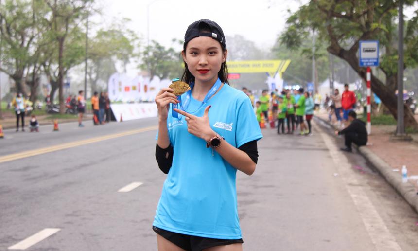 Chị Hồ Thị Ngọc Hiếu (FPT Software) tự tin khoe tấm huy chương ở cự ly 21 km vừa giành được.