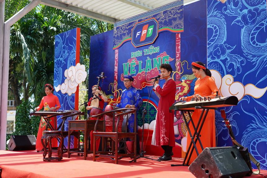 """Đúng 11h, chương trình """"Rước Trạng về làng"""" lần đầu được tổ chức online tại """"Đình làng"""" FPT Tân Thuận 2, (quận 7, TP HCM) đồng thời phát trực truyến trên Workplace ở nhóm Chungta news và trên Facebook qua fanpage Fun4Fun. Mở đầu chương trình là tiết mục liên khúc nhạc xuân đan xen nét cổ truyền và hiện đại do ban nhạc Dân Tộc - gồm những giảng viên tài năng đến từ FPT Education - biểu diễn."""