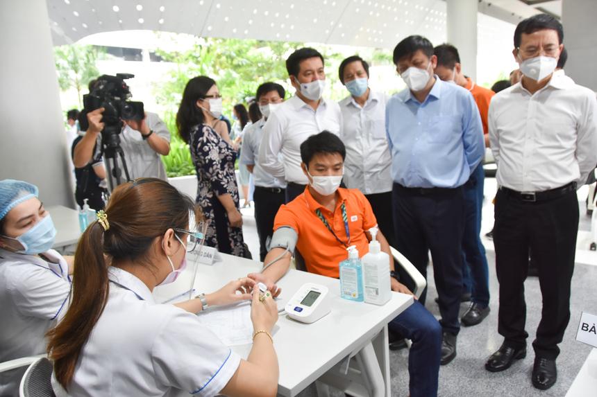 """Hơn 30 nhân viên y tế của các bệnh viện ở thành phố có mặt từ sớm để thực hiện công việc.Bác sĩ Lê Huy Hùng, Bệnh viện Nguyễn Tri Phương kiểm tra sức khoẻ và tư vấn cho nhân viên công ty trước khi tiêm. """"Quy trình này rất quan trọng. Đây là căn cứ để các bác sĩ theo dõi tình trạng sức khỏe, đặc biệt các trường hợp có tiền sử bệnh lý, dị ứng…"""", ông nói."""